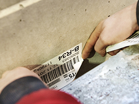 Worker puts on a label on a box